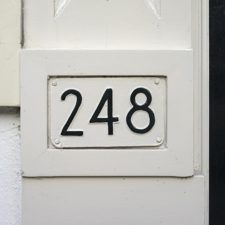 house number two hundred and forty-eight embossed in a metal plackard. Over painted with black.