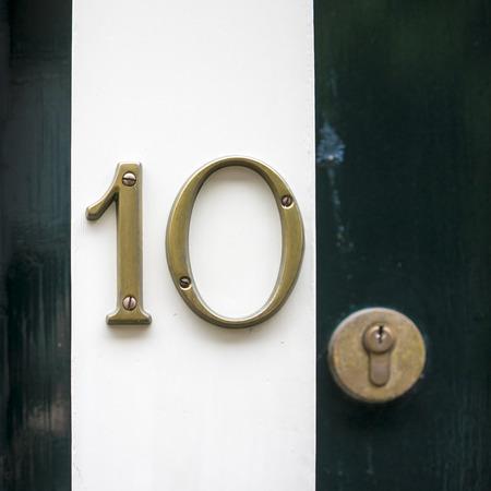 number ten: Bronze house number ten. Separate numerals on a doorpost