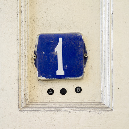 enameled: Enameled house number one. White numeral on a blue background