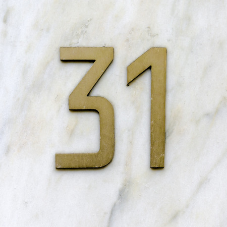cast metal type: bronze house number thirty one on a marble background Stock Photo