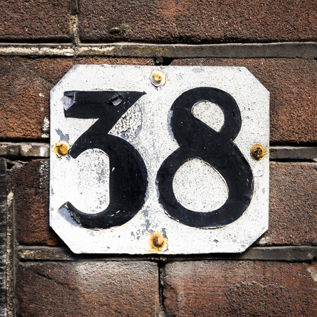 House number thirty eight. Black numerals on a white plate.