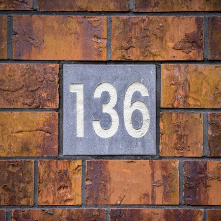 House number one hundred and thirty six, engraved in natural stone. photo