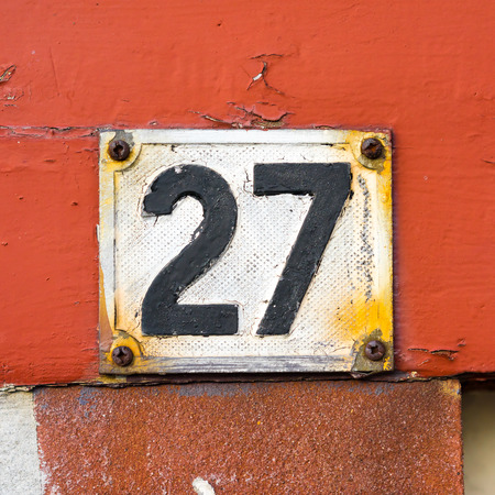 weathered house number twenty seven made of cast aluminum and painted over photo