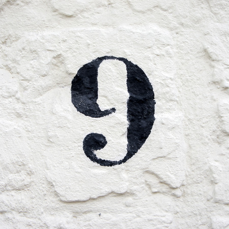 stucco house: hand painted house number ninen. black numeral on a white stucco wall