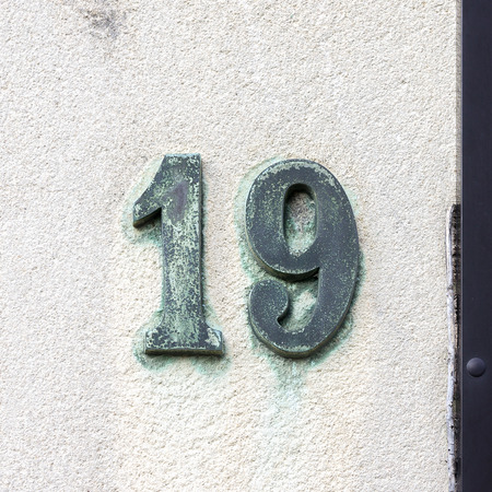 Bronze house number nineteen on a platered wall