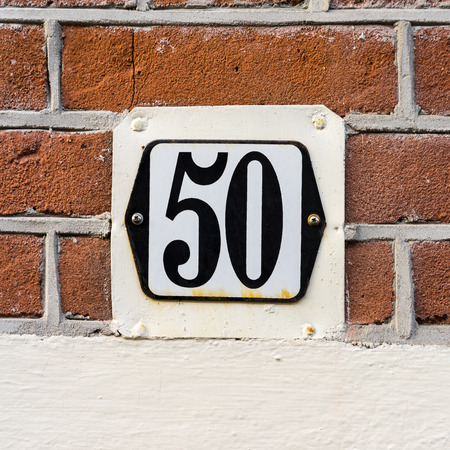 2 50: Enameled house number fifty. Black lettering on a white background.