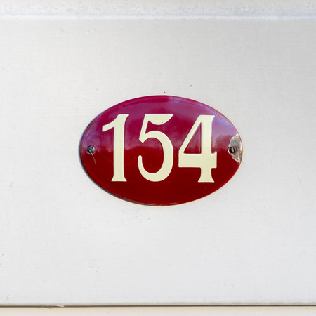 four in one: House number one hundred and fifty four on a enameled oval red plate