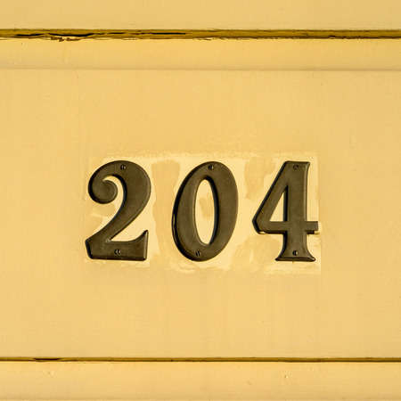 cast metal type: bronze house number two hundred and four. Stock Photo