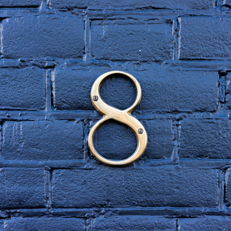 Gold colored house number eight Stock Photo