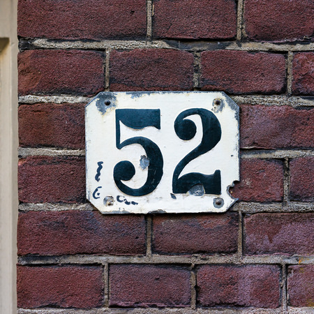 house number fifty two. Black numerals on a white plate photo