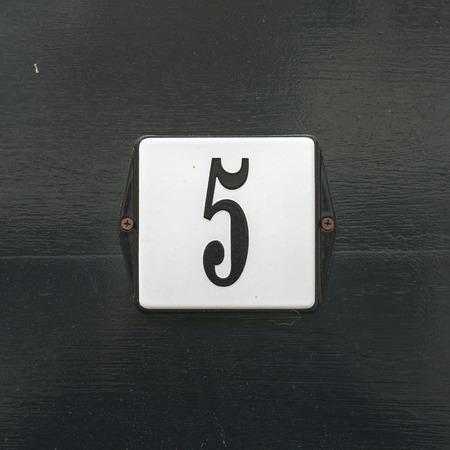 signage: Enameled house number five
