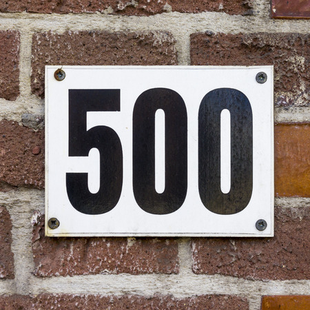 signage: House number five hundred. Black numerals on a white background Stock Photo