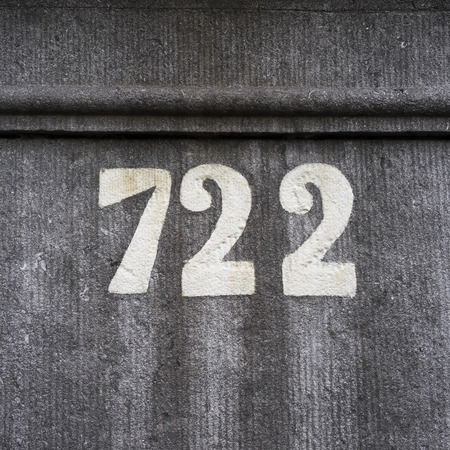 twenty two: House number seven hundred and twenty two (722), hand painted on a stone wall.