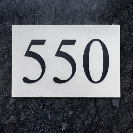 numerals: house number five hundred and fifty (550) engraved in a plastic plate. Black numerals on a white background.
