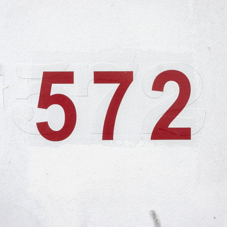 seventy two: house number five hundred and seventy two. Red adhesive lettering on a white background.