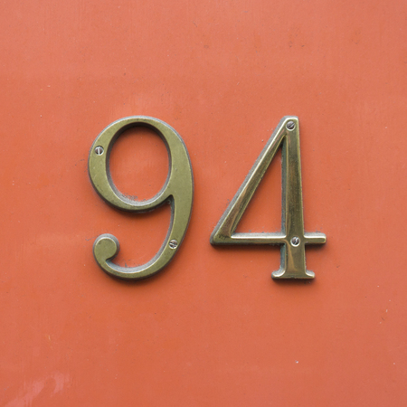 cast metal type: Bronze house number ninety four. Stock Photo