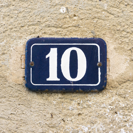 enameled: enameled house number ten. White numerals on a blue background. Stock Photo