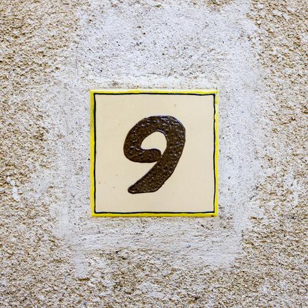numero nueve: número de casa cerámica nueve. Foto de archivo