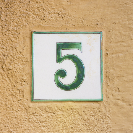 signage: Ceramic house number five on a plastered wall Stock Photo