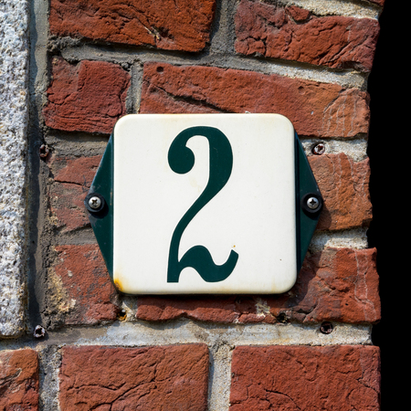enameled: enameled house number two, green numeral on a white background.