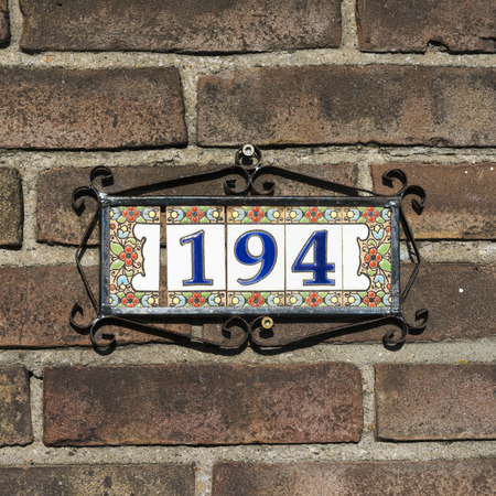 ceramic tiles: house number one hundred and ninety four, on five ceramic tiles.