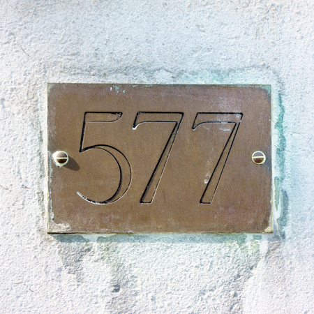 house number five hundred and seventy seven engraved in a brass plate