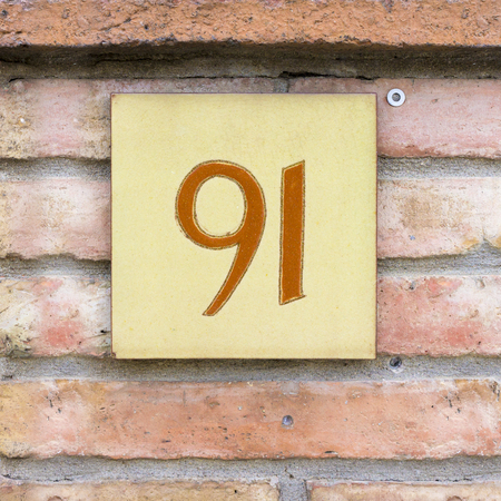 numerals: House number ninety one, orange numerals on a ceramic tile.