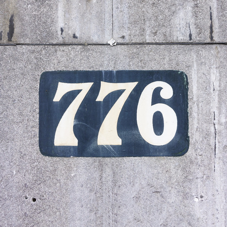 signage outdoor: house number seven hundred and seventy six, painted on a stone wall
