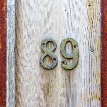 cast metal type: bronze house number eighty nine on a wooden plank