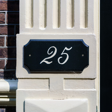 signage outdoor: House number twenty fife, Hand painted on a pane.