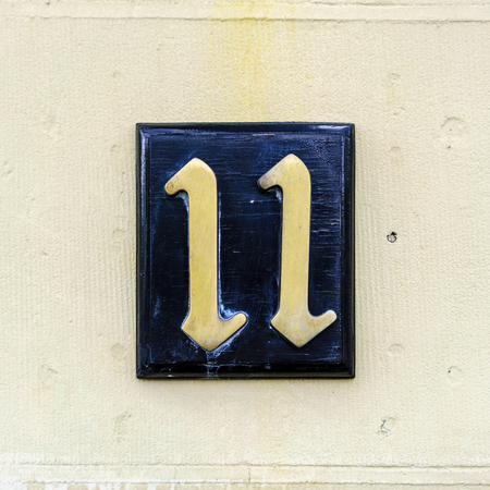 cast metal type: bronze house number eleven on a wooden plank Stock Photo