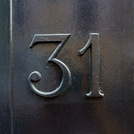 cast metal type: house number thirty one painted black