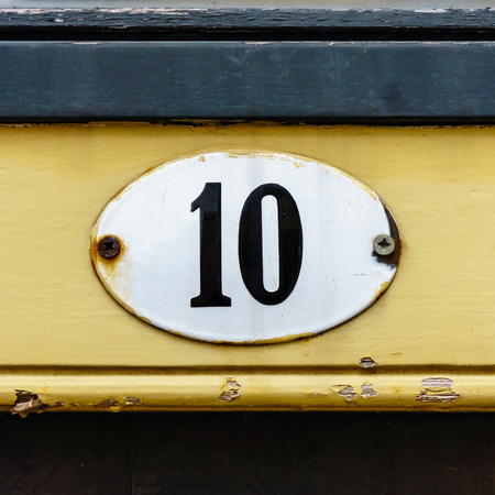 enameled: Enameled house number ten on an oval plate. Stock Photo