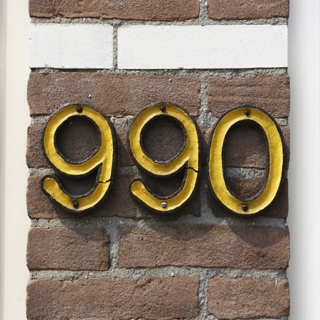Ordinal: Ceramic house number nine hundred and ninety Stock Photo