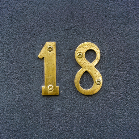 Brass house number eighteen on a plastered wall. Stock Photo