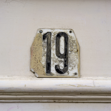 nineteen: House number nineteen, damaged and dirty Stock Photo