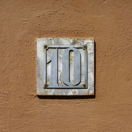 number ten: House number ten cut out of a metal plate. Stock Photo