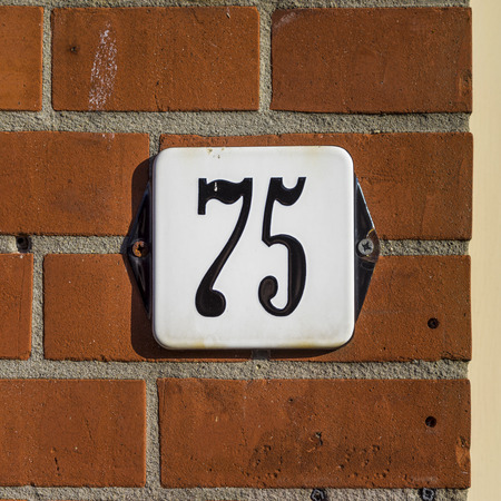 Ordinal: Enameled house number seventy five Stock Photo