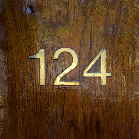 Brass house number one hundred and twenty four on a wooden panel