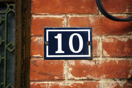 Ordinal: Enameled house number ten on a red brick wall Stock Photo