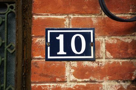 number ten: n�mero de la casa esmaltado diez en una pared de ladrillo rojo Foto de archivo