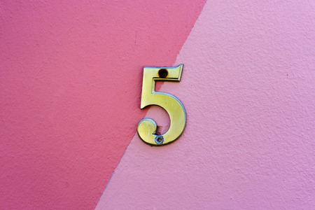 Ordinal: brass house number five on a pink wall Stock Photo
