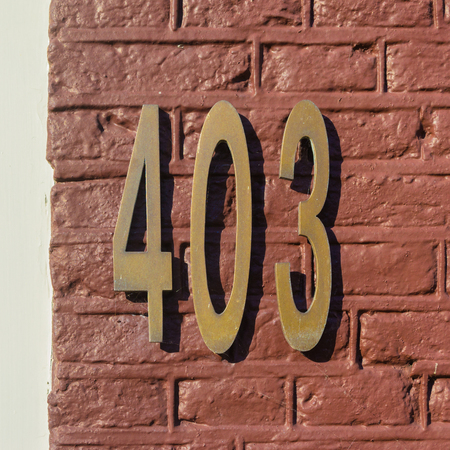 Brass house number four hundred and three Stock Photo