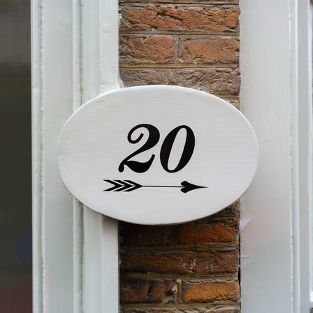 house number twenty (20) above an arrow pointing right