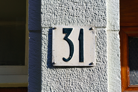 Ordinal: house number thirty one (31) embossed in a metal plate.
