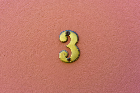 plastered wall: House  number three on a pink plastered wall. Stock Photo