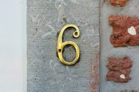 Ordinal: Brass house number six on a stone wall