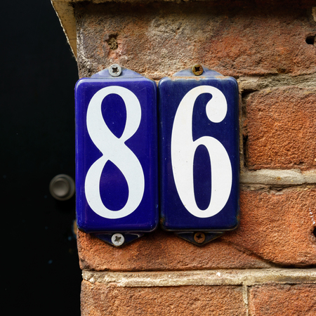 Ordinal: enameled house number eighty six. Stock Photo