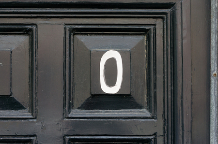 house number zero painted on a door panel