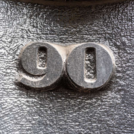 Stone carved house number ninety (90), painted black Stock Photo